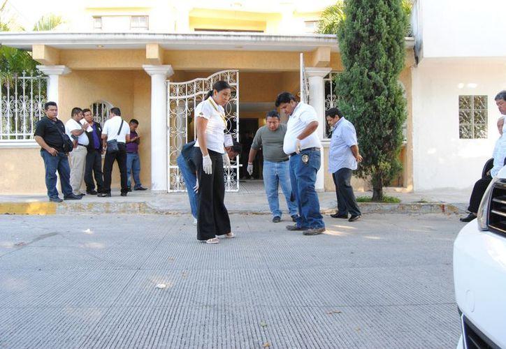 Elementos de la Dirección de Servicios Periciales recaban evidencia a la entrada del domicilio de la víctima. (Redacción/SIPSE)