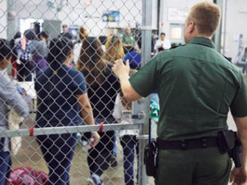 A U.S. Border Patrol agent watches as people who've been taken into custody related to cases of illegal entry into the United States, stand in line at a facility in McAllen, Texas. (AP)