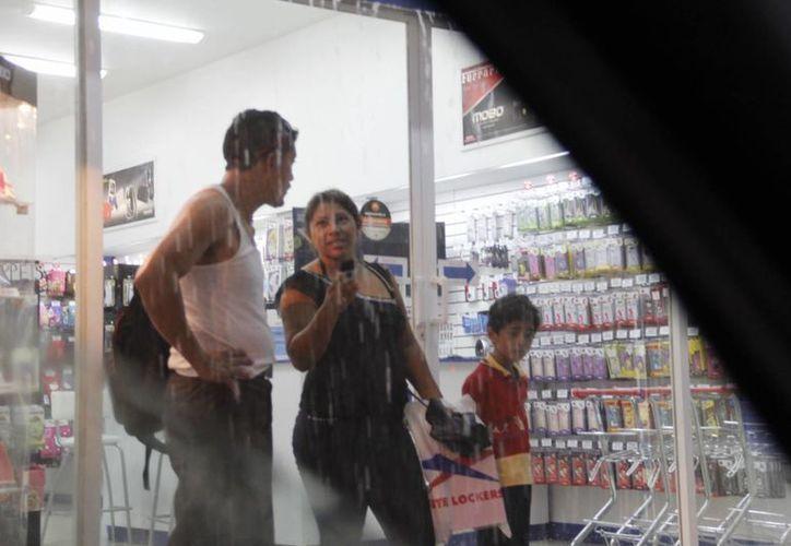 La tormenta obligó a la gente a buscar refugio en comercios del centro de la ciudad. (Juan Albornoz/SIPSE)