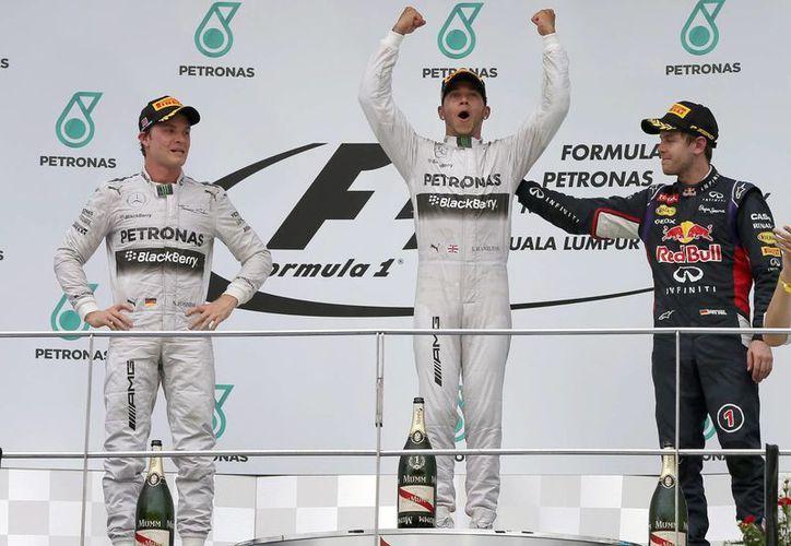 El piloto británico de Fórmula Uno, Lewis Hamilton(c), celebra el triunfo conseguido hoy en Sepang, Malasia, junto a Nico Rosberg (i) y Sebastian Vettel. (EFE)