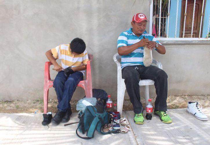 Mariano Ek Tun, que ha sustentado a su familia a través del oficio de reparación de calzado, enseña a su hijo a hacerlo. (Jesús Caamal/SIPSE)
