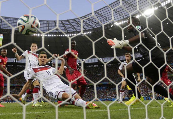 Histórico. Con esta barrida, Miroslav Klose (i) peinó una pelota desde un tiro de esquina y anotó su gol 15 en Mundiales. (Foto: AP)