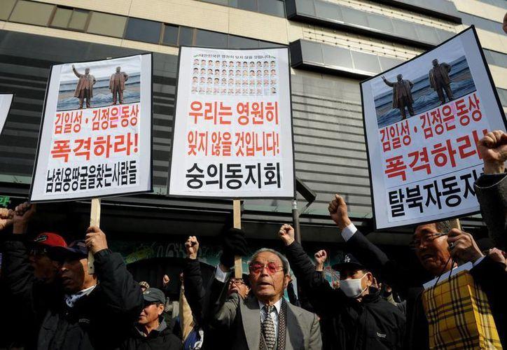Activistas surcoreanos muestran pancartas y corean consignas durante una manifestación contra Corea del Norte ayer. (EFE)