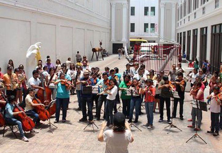 Unos 60 jóvenes de la Orquesta Sinfónica Juvenil de Yucatán se instalaron en el Pasaje Revolución e 'irrumpieron' con su música en el corazón de Mérida. (Cortesía)
