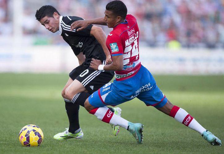 Uno de los dos goles del colombiano James Rodríguez (de camisa oscura), del Real Madrid, ante Granada fue un poema de gol. (Foto: AP)