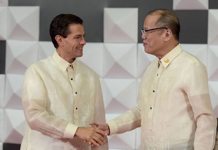 El presidente Enrique Peña Nieto al saludar al mandatario de Filipinas, Benigno Aquino III, al asistir a la Cena de Bienvenida que se ofreció a los líderes de las 21 economías que conforman la APEC. (Notimex)