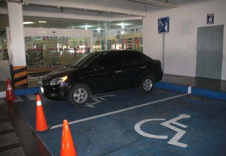 Los establecimientos no cumplen con otorgar el 20% de los cajones de estacionamiento para los discapacitados. (Redacción/SIPSE)