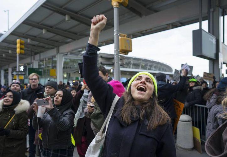 Una manifestante levanta el puño y grita durante una protesta en el aeropuerto internacional John F. Kennedy en Nueva York, depsués de que dos refugiados iraquíes fuesen detenidos al intentar entrar al país. (AP/Craig Ruttle)