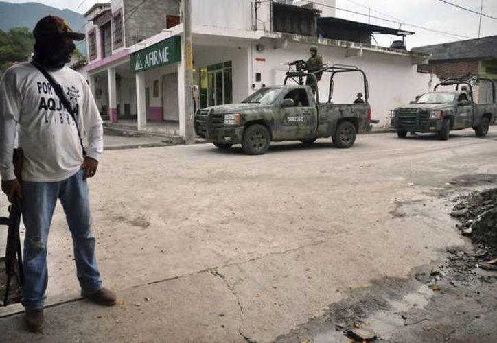 Hombres armados, denominados autodefensas, tomaron el municipio de Parácuaro, Michoacán, donde 'se respira' tensión. Foto de archivo de policía comunitaria de Aquila, en el mismo estado. (SIPSE.com)