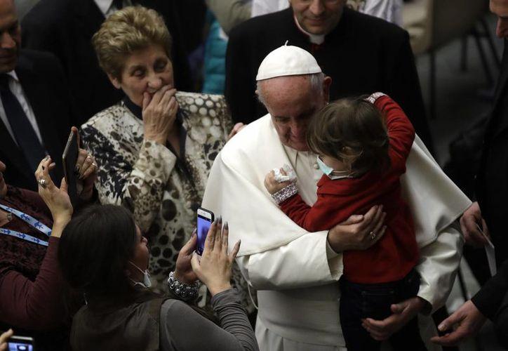 El Papa Francisco, seguido por Mariella Enoc, presidenta de la junta directiva del hospital pediátrico Bambino Gesu, de fondo, abraza a un niño durante una audiencia especial concedida a algunos de los empleados del hospital pediátrico Bambin Gesu. (AP/Alessandra Tarantino)