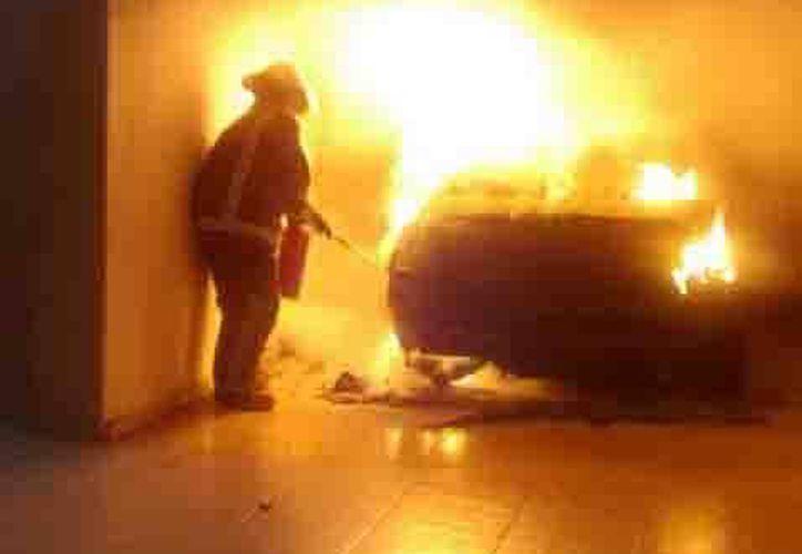 Un bombero se encargó de apagar las llamas que consumían el vehículo. (Redacción/SIPSE)