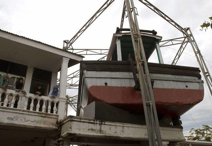 En Lampulo, un barrio de pescadores de la ciudad, un barco permanece incrustado en el techo de una casa, donde hace 10 años 59 vecinos buscaron refugio ante la avalancha de agua y se salvaron gracias a la inesperada aparición de la embarcación. (EFE)