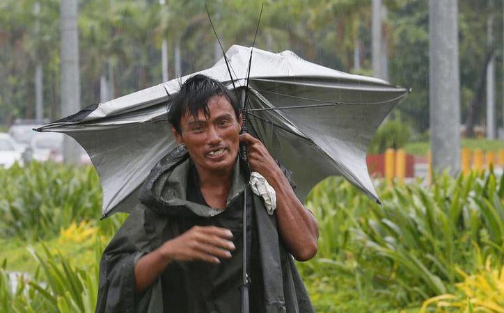 Un hombre camina por un malecón con un paraguas roto mientras cae una llovizna causada por el tifón Sarika, este domingo en Manila, Filipinas. (AP Foto/Bullit Marquez)