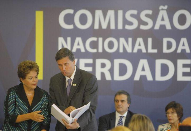 La presidenta brasileña, Dilma Rousseff, recibe de manos de Pedro Dallari, coordinador de la Comisión de la verdad de Brasil, el informe final que investigó las violaciones de derechos humanos durante la última dictadura (1964-1985). (Archivo/EFE)