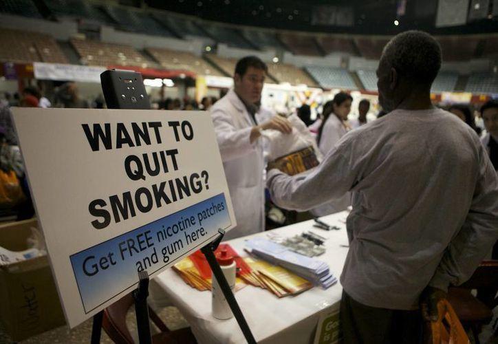 Los fumadores que no tienen seguro médico reciben gratuitamente parches y chicles de nicotina en el Remote Area Medical (RAM) en el interior de la clínica de Los Angeles Sports Arena de Los Angeles. (Agencias)