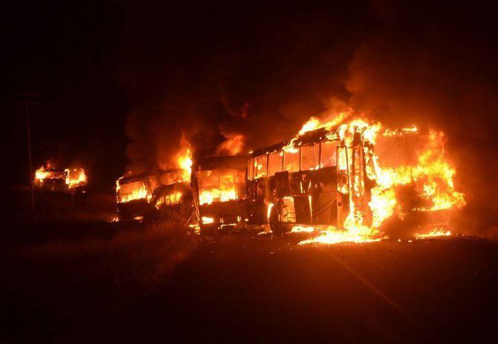 Los nueve camiones consumidos por las llamas que se encontraban en poder de los normalistas ocasionaron más daños que los diez atacados por la delincuencia. (Notimex)