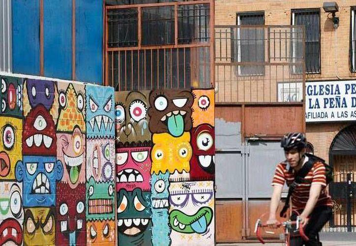Un ciclista pasa cerca de unos murales en Bushwick, un vecindario de Booklyn, en NY, donde fue baleado un adolescente mexicano. Imagen de contexto, solo para fines ilustrativos. (AP/Kathy Willens)