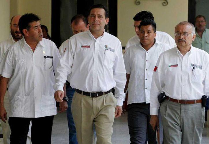 Imagen de archivo del ex gobernador de Tamaulipas, Eugenio Hernández Flores, centro, al llegar a una conferencia de prensa en el palacio de gobierno en Ciudad Victoria en 2010. El jueves 18 de junio de 2015 se reveló una acusación en su contra por lavar dinero y ayudar a una operación de envío de dinero no autorizada. (Foto AP/Eduardo Verdugo, archivo)