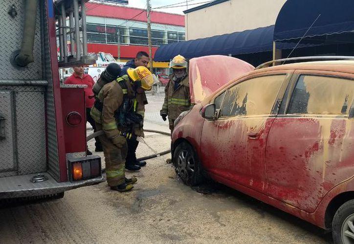 El auto Spark comenzó a incendiarse sobre el bulevar Playa del Carmen. (Foto: Redacción/SIPSE)