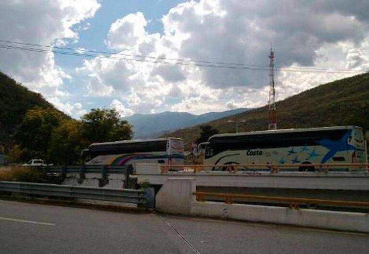 Imagen tomado del sitio Milenio Digital en la que pueden verse autobuses que este sábado fueron secuestrados por normalistas de Ayotzinapa.