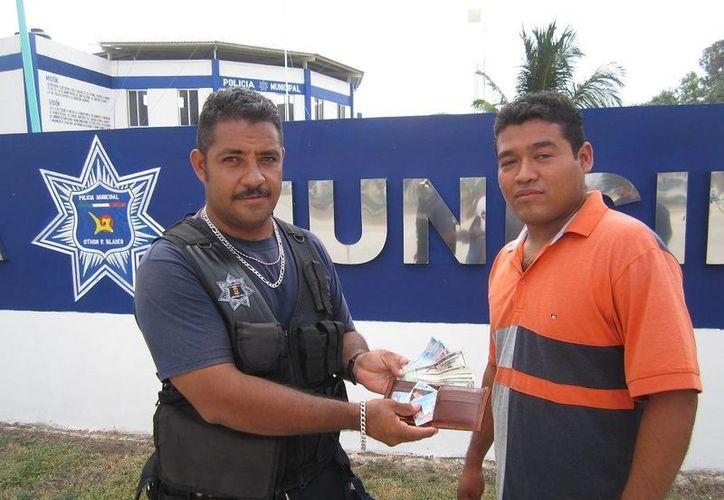 El policía Rubén Franklin Chipoli, en el momento de la entrega de la cartera. (Harold Alcocer/SIPSE)