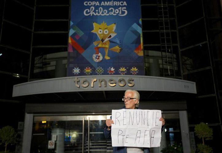 Frente a la compañía Torneos y Competencias, un hombre sostiene un letrero que pide al presidente de la Asociación Argentina de Soccer dejar su puesto, en alusión al escándalo por corrupción en la FIFA que este viernes derivó en el allanamiento en Buenos Aires de empresas de ejecutivos prófugos. (Foto: AP)