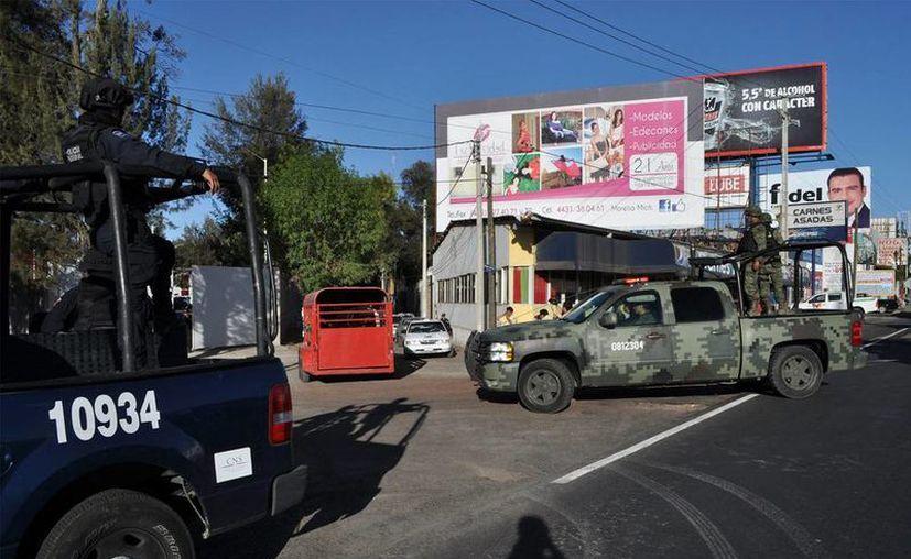 Esta mañana fue detenido un sobrino de <i>El Kike</i> Plancarte, líder de Los Caballeros Templarios. Manuel Plancarte está acusado del asesinato de dos niños y de tráfico de órganos. En la foto, Policía Federal y Ejército patrullan las calles de Morelia, Michoacán. (Notimex)