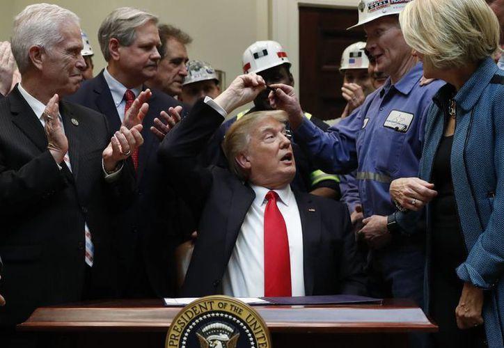 El presidente Donald Trump regala la pluma con la que firmó la Resolución H.J. 38, desaprobando la regla presentada por el Departamento del Interior de los EU conocida como la Regla de Protección de Flujo. (AP/Carolyn Kaster)