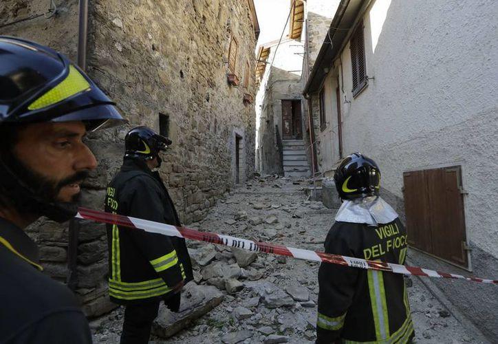 Los bomberos se colocan fuera de una casa afectada por el sismo en Pretara, cerca de Arquata del Tronto. (AP/Andrew Medichini)