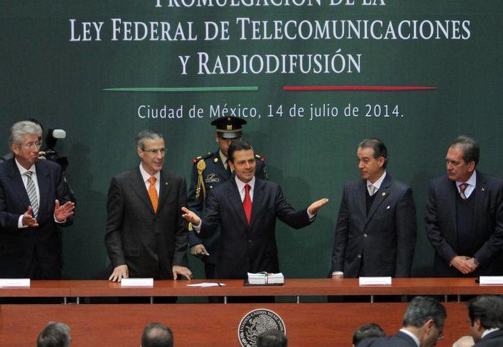 El presidente Enrique Peña firmó ayer el decreto por el que se promulga la Ley Federal en Telecomunicaciones, en Palacio Nacional. (Notimex)