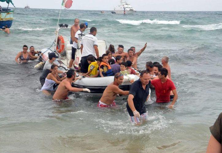 La Guardia Costera italiana y bañistas ayudando durante el rescate de 160 inmigrantes que llegaron a la playa de Morghella, al sureste de Sicilia, Italia. (EFE/Archivo)