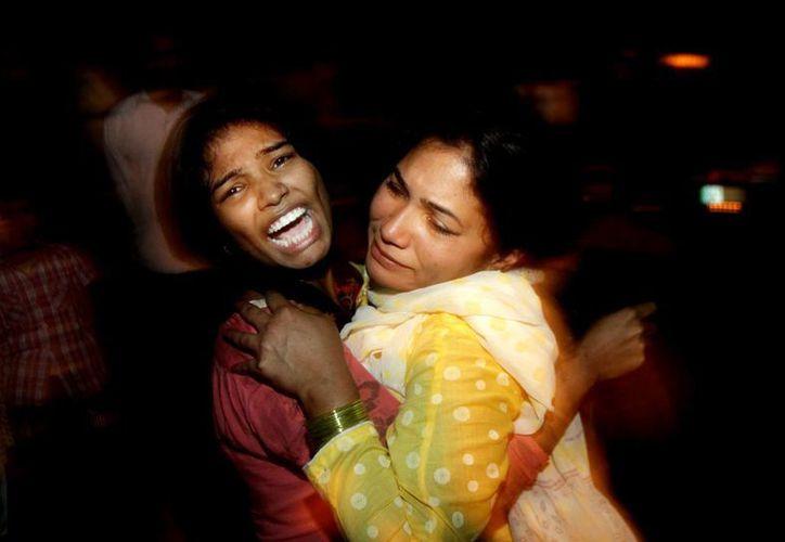 Dos mujeres se abrazan mientras lloran por la muerte de un miembro de su familia durante el ataque suicida en un parque de Pakistán. (Agencias)