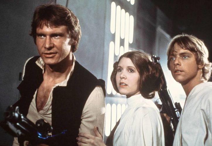Esta imagen publicitaria difundida por la 20th Century-Fox Film Corporation muestra, de izquierda a derecha, a Harrison Ford como Han Solo, Carrie Fisher en el papel de la princesa Leia Organa y Mark Hamill como Luke Skywalker. (Agencias)