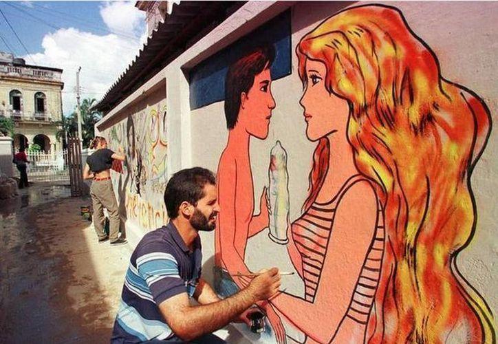 Trabajadores del Ministerio de Salud Pública de Cuba pintan un mural en La Habana como parte de una campaña contra el VIH y el Sida. (José Goitia/Canadian Press)