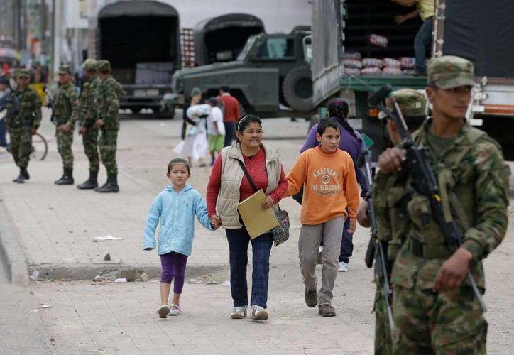 Una familia camina por la población de Soacha, donde grupos de soldados realizan patrullajes. (AP)