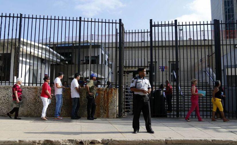 Un guardia de seguridad permanece en las afueras de la Sección de Intereses de Estados Unidos en Cuba donde gente hace fila para obtener una visa en La Habana, Cuba. (AP Photo/Desmond Boylan)