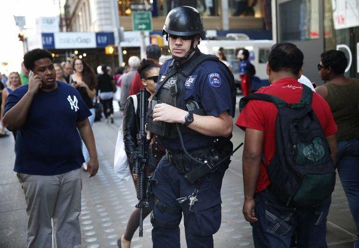 Un oficial de policía fuertemente armado camino a través de las multitudes en Times Square, en Nueva York. La Policía intensificó la seguridad en medio de amenazas del Estado Islámico. (Agencias)