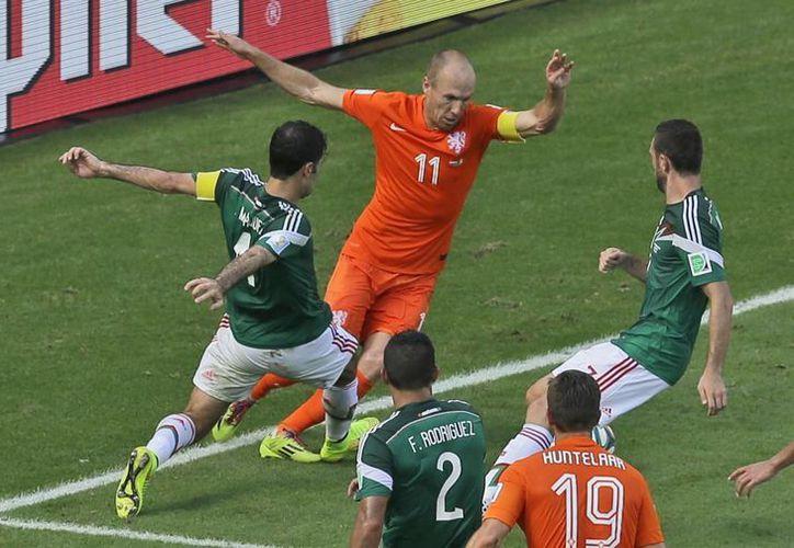 Márquez apenas tocó a Robben, pero el desvergonzado silbante marcó penal que determinó la victoria holandesa y la eliminación mexicana. (Foto: AP)