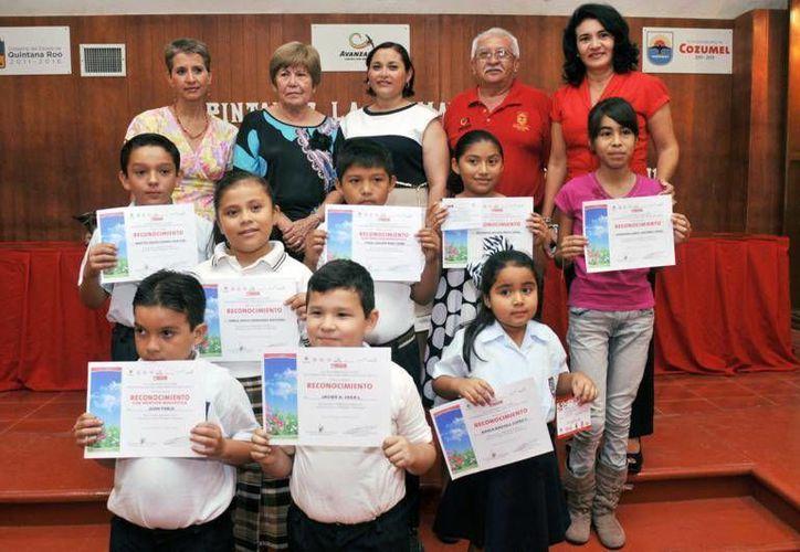 Los menores estudiantes con sus reconocimientos, acompañados de las autoridades. (Cortesía/SIPSE)