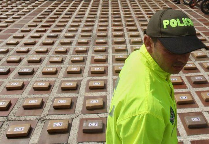 Miembros de la Policía custodian kilos de cocaína incautados en la ciudad de Cali, Colombia, pertenece a la banda Los Urabeños. (Archivo/EFE)
