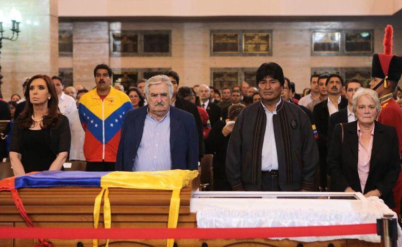 La mandataria argentina Cristina Fernández, el uruguayo José Mujica y  el boliviano Evo Morales, junto al féretro de Chávez. (Agencias)