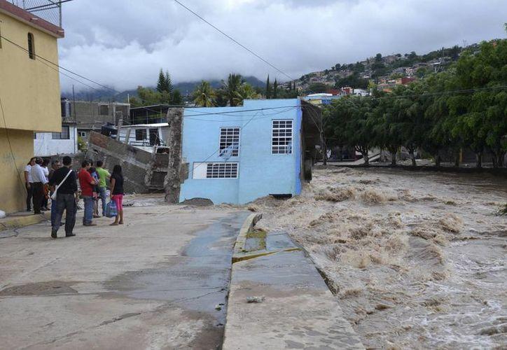 """Las fuertes lluvias provocadas por la tormenta tropical """"Manuel"""" y el huracán """"Ingrid"""" dejan graves dañoscomo el desborde del río Huacapa en Chilpancingo, Guerrero. (Agencias)"""