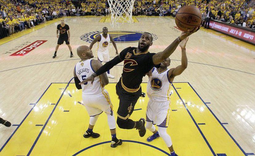 LeBron James (c) durante una de sus espectaculares jugadas frente a los Golden State Warriors en el séptimo juego de la final de la NBA, en junio de este año. (AP)