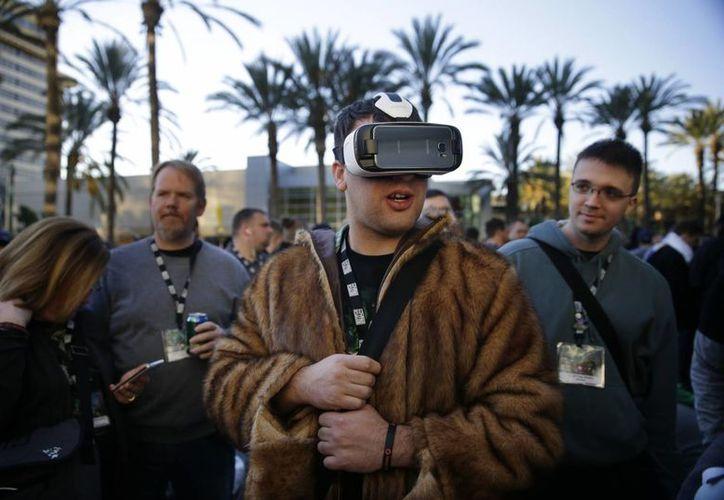 Un joven prueba las gafas Gear VR de Samsung, mientras espera a entrar a la BlizzCon el pasado 6 de noviembre, en Anaheim, California. (Agencias)