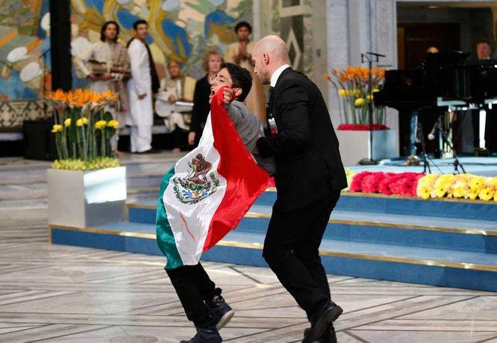 Acreditado como periodista, un joven, con una bandera de México manchada de sangre en las manos, irrumpió en la ceremonia de los Premios Nobel de la Paz, entregados a Malala Yousafzai y Kailash Styarth.