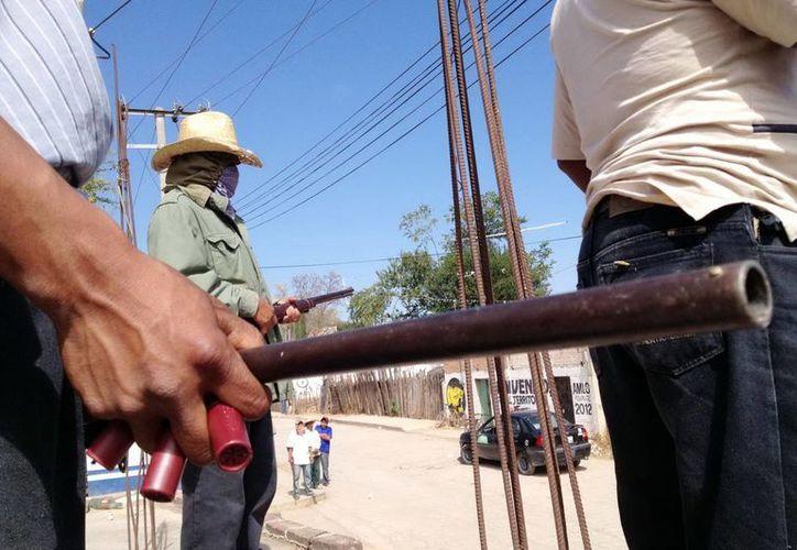 Habitantes de Atliaca y Acatempa del municipio de Tixtla de Guerrero en uno de los retenes que colocoraon. (Archivo/Notimex)