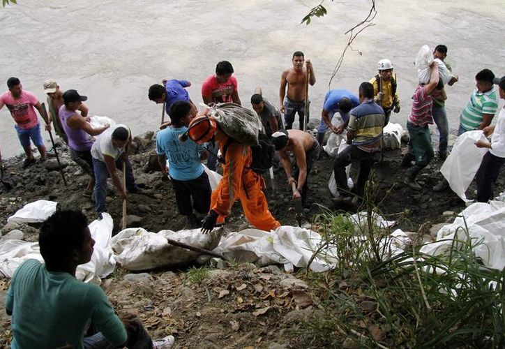 Mineros excavan a la orilla del río Cauca en busca de 16 mineros que se encuentran atrapados en Riosucio, departamento de Caldas, Colombia. (EFE)