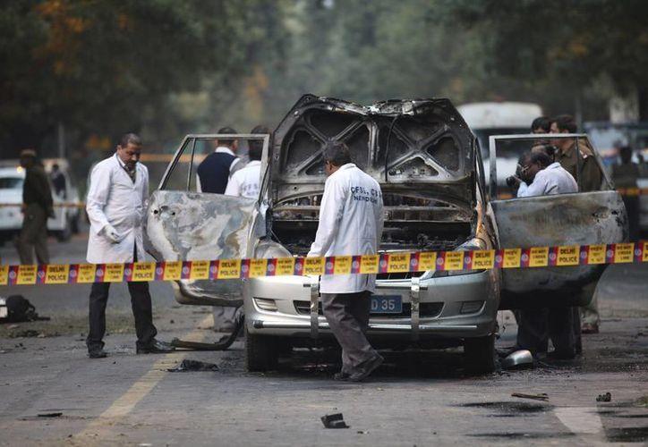 Peritos de la india revisan el autobomba utilizado en el atentado. (EFE)