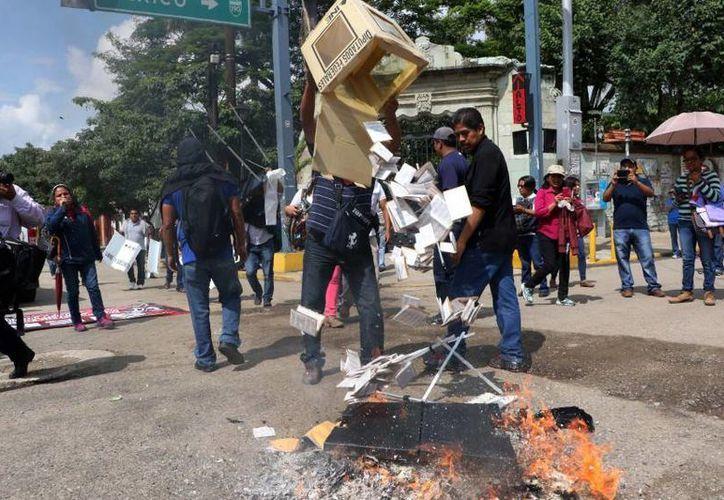 Profesores de la Sección de la CNTE queman material electoral en Oaxaca, el domingo 7 de junio de 2015. (Archivo AP/Luis Alberto Hernández)