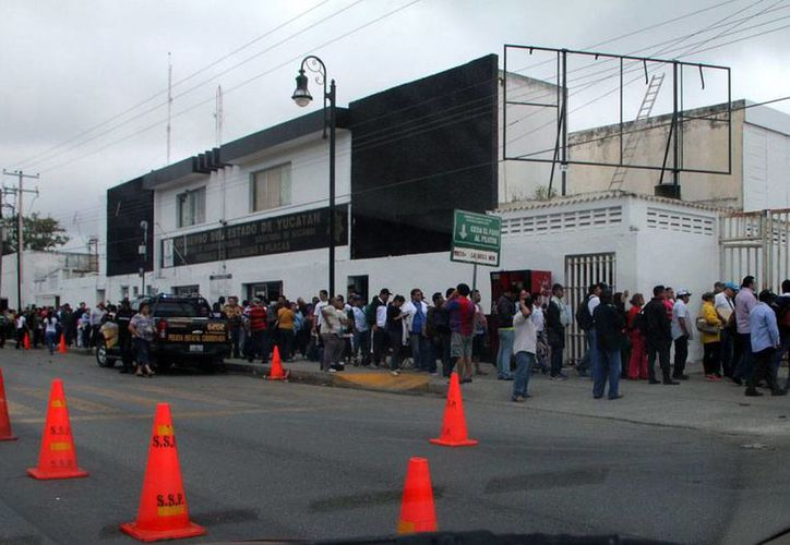 Propietarios de vehículos hacen largas filas para realizar trámites en las oficinas de la Secretaría de Seguridad Pública, a un costado de la expeniteciaría, a unos días del cierre de 2014. (José Acosta/SIPSE)